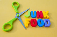 Cut out junk food. Text 'junk food' in colorful uppercase letters with scissors alongside creating concept of cutting down on junk food for health reasons stock image