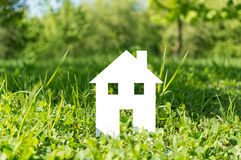Cut out paper house on green grass Royalty Free Stock Image