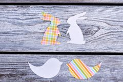 Cut out paper rabbits and birds. Papercut animalistic silhouettes. Color patterned paper figurines. Easter festive preparations stock image
