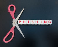 Cut out phishing. Scissors around text `phishing` inscribed on  small white cubes in red upper case letters; concept of finding details of someone`s identity on Stock Photography