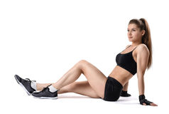 Cut-out portrait of young strong muscular woman sitting on the floor and rested after training stock photography