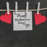 Cut out of red paper hearts hang on the rope on the little primako, greetings happy Valentine`s day Royalty Free Stock Photos