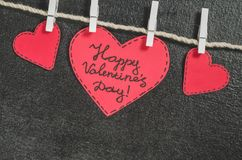 Cut out of red paper hearts hang on the rope on the little primako, greetings happy Valentine`s day Stock Images