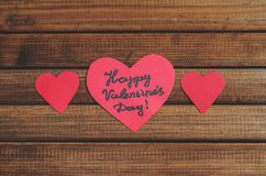 Cut out of red paper hearts on wooden background, congratulation with Valentine`s day Royalty Free Stock Photography