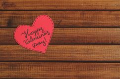 Cut out of red paper hearts on wooden background, congratulation with Valentine`s day Royalty Free Stock Photos