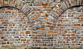 Cut out rocks in wall with arched brickwork Royalty Free Stock Image