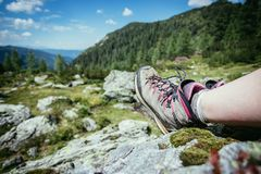 Alpine boots in foreground, idyllic mountain landscape in the blurry background. Cut out of a woman in hiking boots who is enjoying the idyllic mountain royalty free stock photo