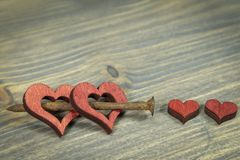 Cut out wooden heart shapes with rusted nail. Wooden hearts connected together with small rusted nail. Cut out wooden heart shapes painted red, viewed in close royalty free stock photos