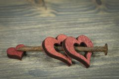 Cut out wooden heart shapes with rusted nail. Wooden hearts connected together with small rusted nail. Cut out wooden heart shapes painted red, viewed in close stock photography