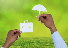 Cut outs of Briefcase and umbrella insurance over grass Stock Images