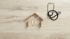 Cut outs of a family with children in a house, conceptual of home insurance. Cut outs of a family with children in a house with a stethoscope lying on a wooden royalty free stock photos