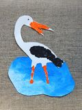 Cut and painted colorful stork bird on linen background stock image