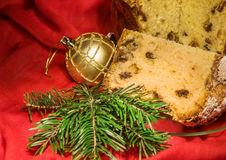Cut panettone, branch of fir tree, golden bauble. Christmas theme. Royalty Free Stock Photography
