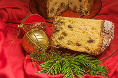 Cut panettone, branch of pine tree and baubles. Christmas theme. Stock Image