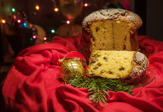 Cut panettone, green branch, baubles, blurred lights. Christmas theme. Royalty Free Stock Photography