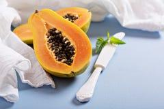 Cut papaya on a blue table Royalty Free Stock Photos