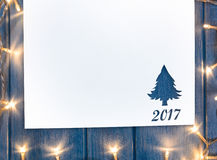 Cut paper with lights in fir-tree shape on table Royalty Free Stock Images
