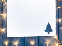 Cut paper with lights in fir-tree shape on table Stock Photography