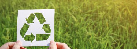 Cut paper with the logo of recycling over green grass Stock Images
