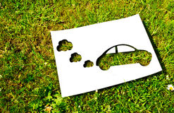 Cut paper, renewable energy concept. White paper cut in the shape of a car on a background of grass. Renewable energy concept Stock Image