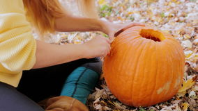 Cut the pattern on the pumpkin. Preparing for Halloween. Young woman carves a pumpkin. Sitting in the yard in the background of yellowing and orange trees stock video footage