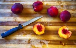 Cut peach over chopping board Stock Image