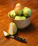 Cut Pear with Pears in Wood Bowl Royalty Free Stock Photography