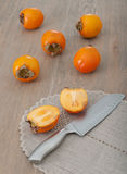 Cut persimmon fruit and knife. Cut in half persimmon fruit with whole kaki and knife on the wooden background stock photos