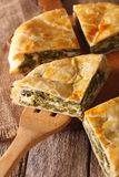 The cut pie spanakopita close-up on. vertical Royalty Free Stock Photos