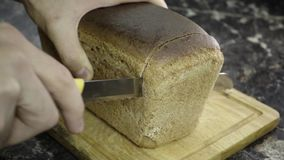 Cut a piece of black bread. With a special knife stock video