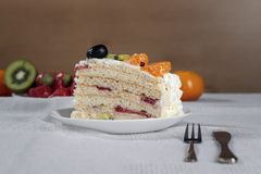 Cut piece of cake made from natural ingredients, fresh kiwi fruit, grapes, tangerine and strawberries stands on a table.  stock photography