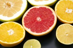 Cut pieces of different citrus fruits on dark background. The cut pieces of different citrus fruits on dark background stock image