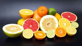 Cut pieces of different citrus fruits on dark background. The cut pieces of different citrus fruits on dark background royalty free stock images