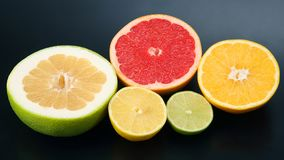 Cut pieces of different citrus fruits on dark background. The cut pieces of different citrus fruits on dark background stock photo