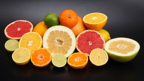 Cut pieces of different citrus fruits on dark background. The cut pieces of different citrus fruits on dark background royalty free stock image