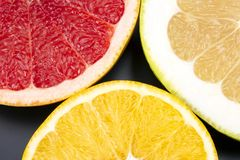 Cut pieces of different citrus fruits on dark background. The cut pieces of different citrus fruits on dark background royalty free stock photos