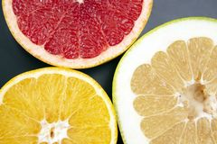 Cut pieces of different citrus fruits on dark background. The cut pieces of different citrus fruits on dark background stock photos