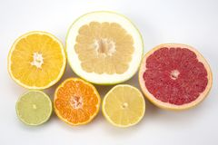 Cut pieces of different citrus fruits on white background. The cut pieces of different citrus fruits on white background royalty free stock photography