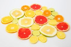 Cut pieces of different citrus fruits on white background. The cut pieces of different citrus fruits on white background stock photos