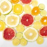 Cut pieces of different citrus fruits on white background. The cut pieces of different citrus fruits on white background stock photography