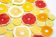 Cut pieces of different citrus fruits on white background. The cut pieces of different citrus fruits on white background stock images