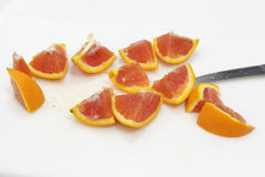 Cut Pieces of Orange on a Cutting Board. One bright orange fruit cut into twelve pieces with a knife on a white plastic cutting board close-up. An orange sliced stock photo