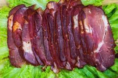 Cut pieces of smoked meat with lettuce Royalty Free Stock Image