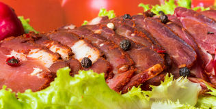Cut pieces of smoked meat with lettuce and pepper Royalty Free Stock Photos