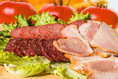Cut pieces of smoked salam and ham with lettuce Stock Photos