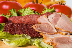 Cut pieces of smoked salam and ham with lettuce Royalty Free Stock Images