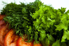 Cut pieces of tomatoes and dill and parsley. Close-up on white Stock Photo