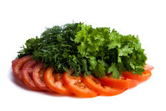 Cut pieces of tomatoes and dill and parsley. Close-up on white Stock Images