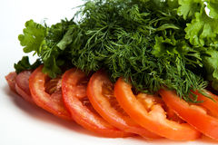 Cut pieces of tomatoes and dill and parsley. Close-up on white Stock Photography