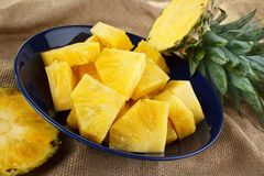 Cut pineapple. On dish with green leaves Royalty Free Stock Photo